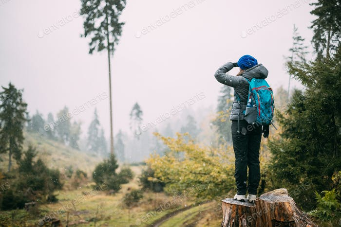 Young Woman Standing On Stump In Forest And Looking Into Distanc
