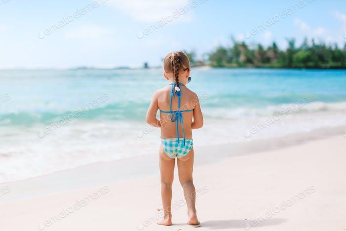Entzückende kleine Mädchen haben Spaß am tropischen Strand während des Urlaubs