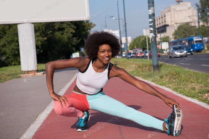 Thumbnail for Portrait of sporty young african american woman stretching outdo