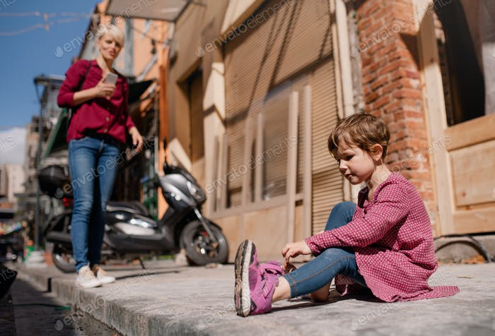 A small girl with mother sitting outdoors on pavement, taking off shoes