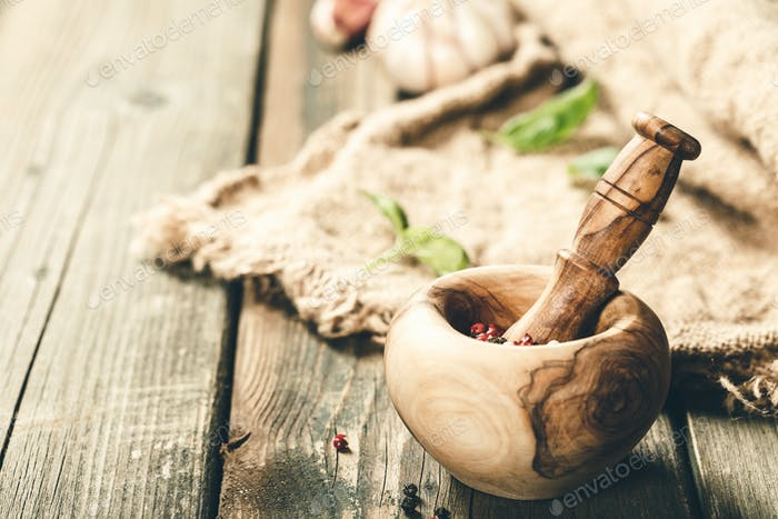 Cooking background. Wooden mortar and pestle, herbs and spices, copy space