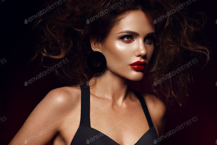 Beautiful face of a fashion model with red lips. Studio portrait