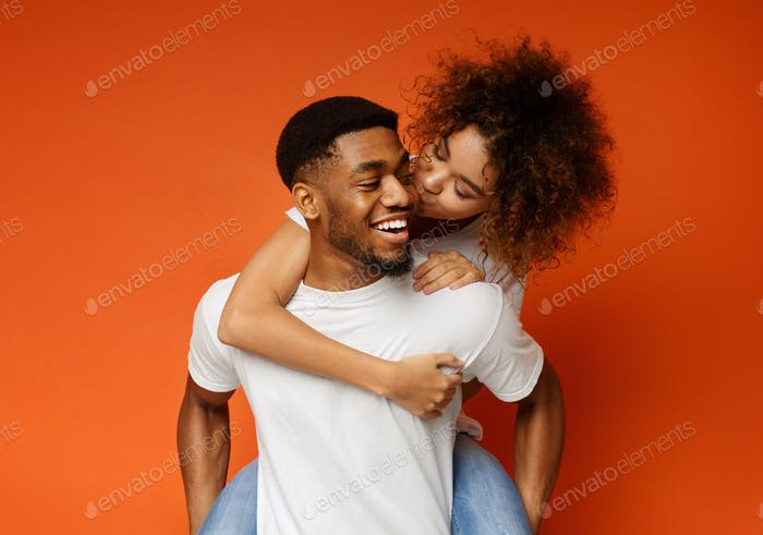 African american millennial couple fooling together, girl kissing her boyfriend
