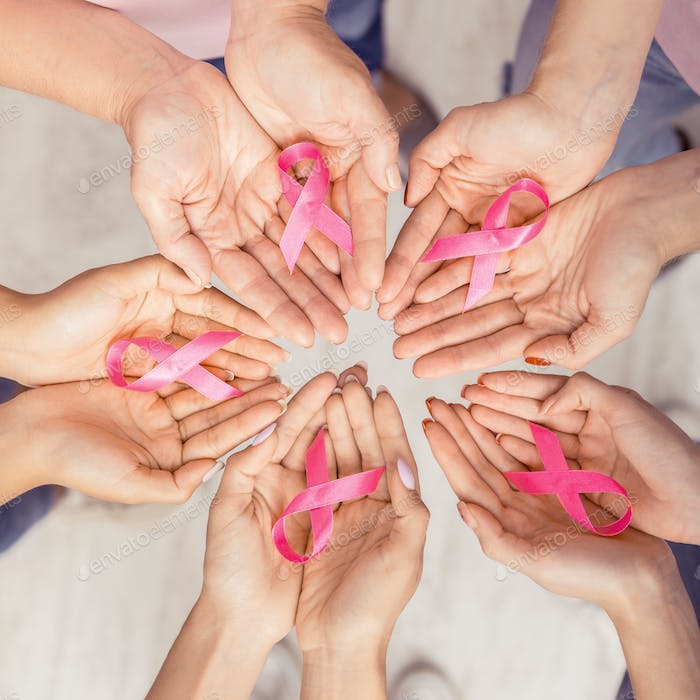 Female Hands Joined In Circle Holding Pink Ribbons, White Background