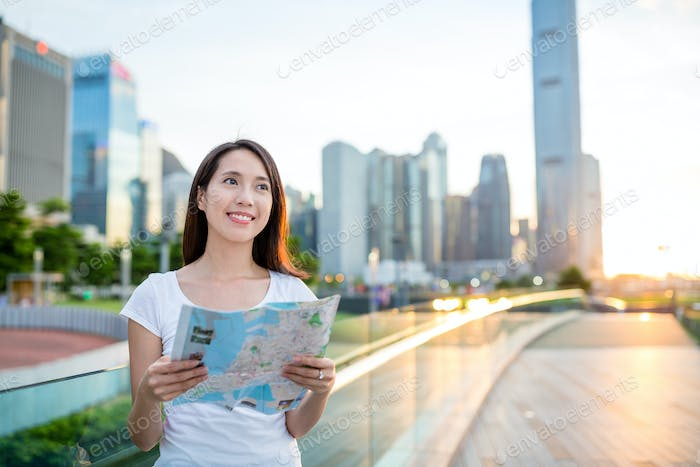 Woman searching location on paper map