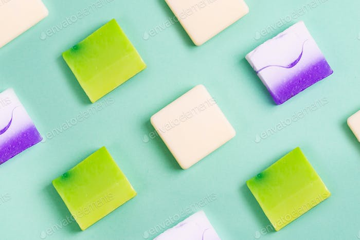 Handmade organic rows of various colorful homemade bar soaps on green
