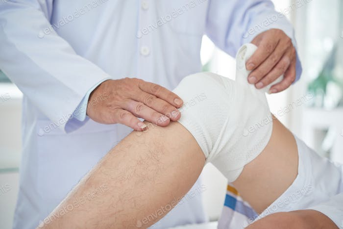 Crop doctor bandaging knee of patient