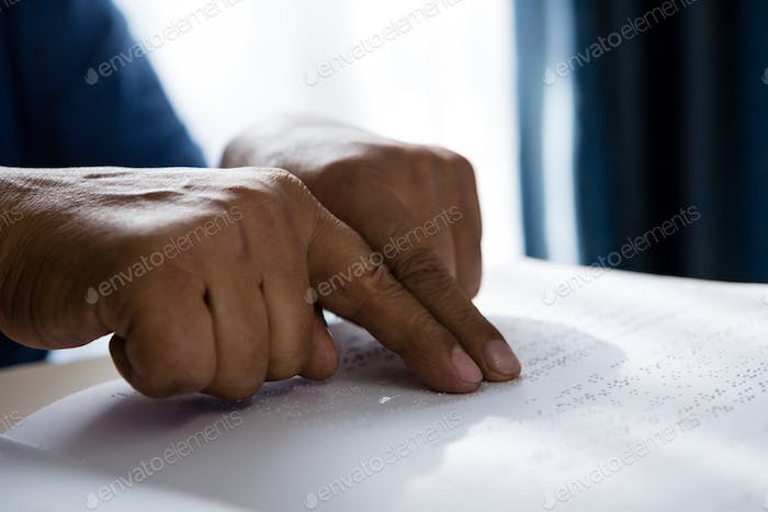 Cropped hands on senior man reading braille book in retirement home