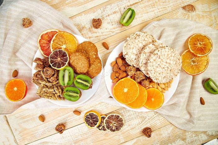 Healthy snacks -  variety oat granola bar,  rice crips, almond,  kiwi, dried orange