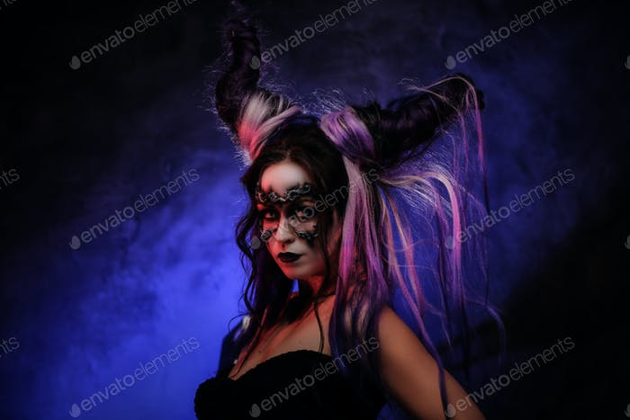 Cosplayer girl wearing dark demonic make up and horns posing in a studio on a dark background