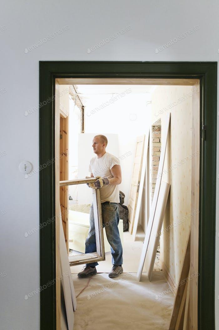 Carpentry carrying window frame seen through doorway in room
