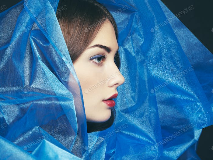 Fashion photo of beautiful women under blue veil