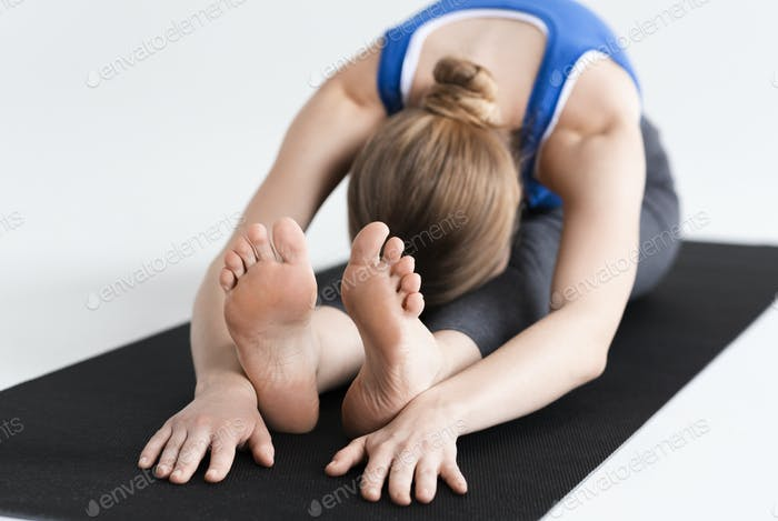 Morning sports practice. Young woman doing stretching or yoga on mat, white background