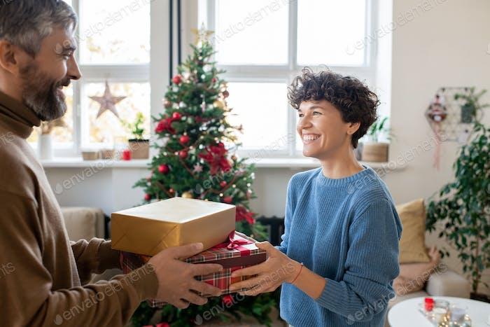 Glücklicher bärtiger Mann, der seiner hübschen Frau zwei Geschenkboxen übergibt, während er sie ansieht