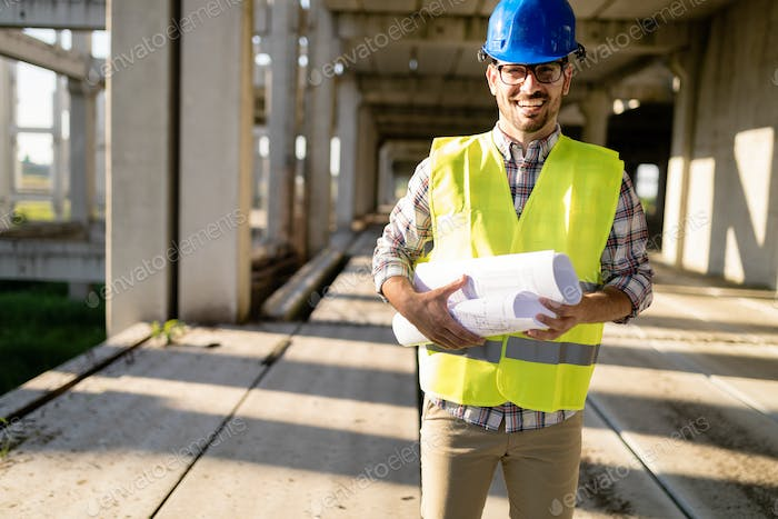Architect holding rolled up blueprints at construction site
