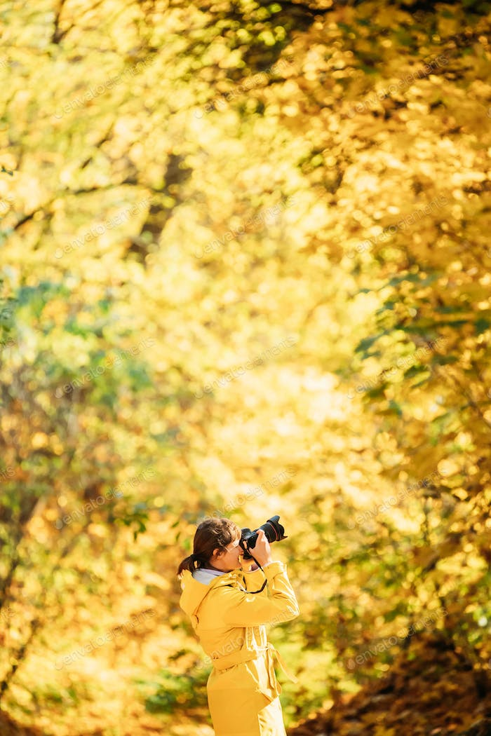 Aurlandsfjellet, Norway. Young Woman Tourist Photographer Taking Pictures Photos Of Autumn Yellow