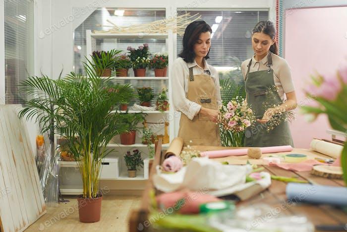 Dos floristas arreglando flores en la tienda