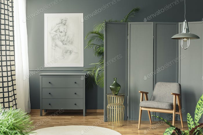 Dark, gray living room interior with a sketch hanging above a wo
