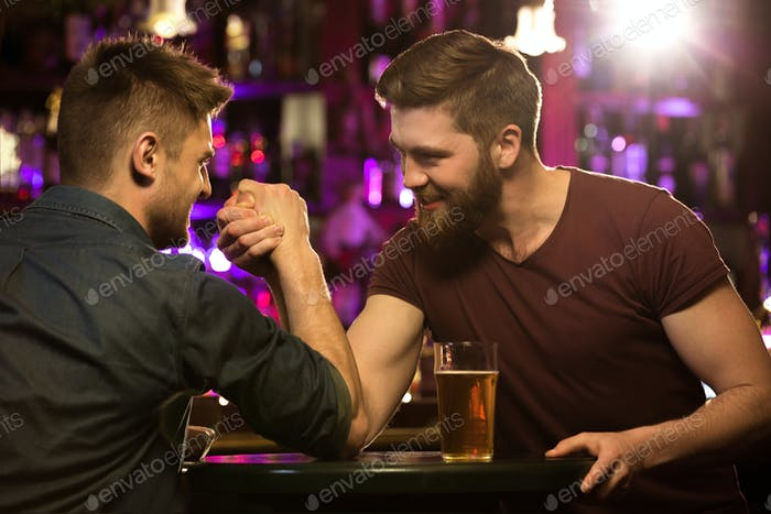 happy male friends drinking draft beer and arm wrestling