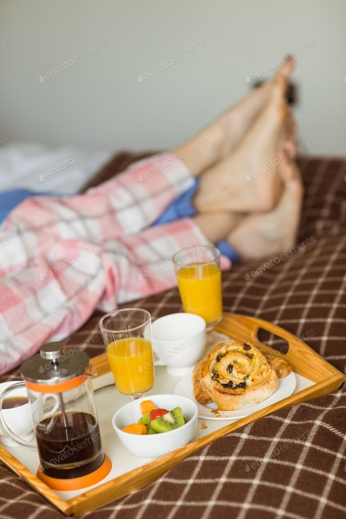 Cute couple having breakfast in bed at home in the bedroom