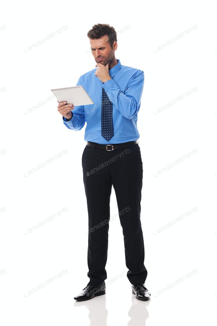 Businessman holding digital tablet and grimacing