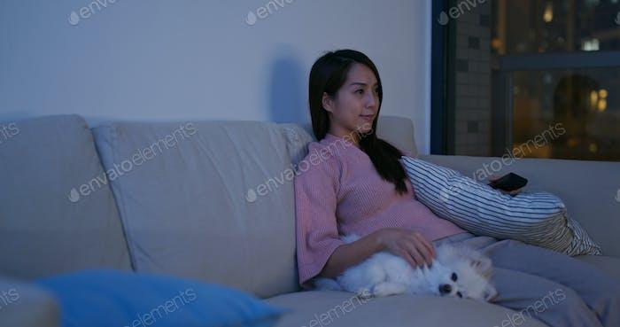 Woman watch tv with her pomeranian dog