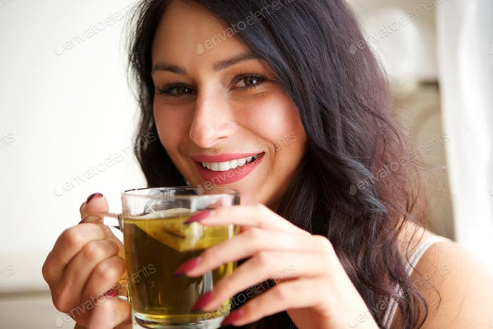 happy woman inside cozy apartment with hot tea