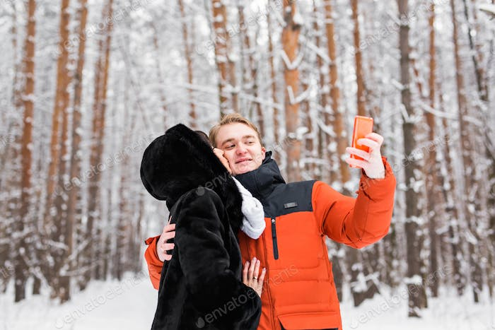 Attractive couple doing selfie outdoors.