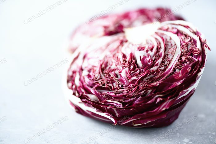Radicchio, purple violet salad on grey concrete background. Copy space, close up. Raw, vegan