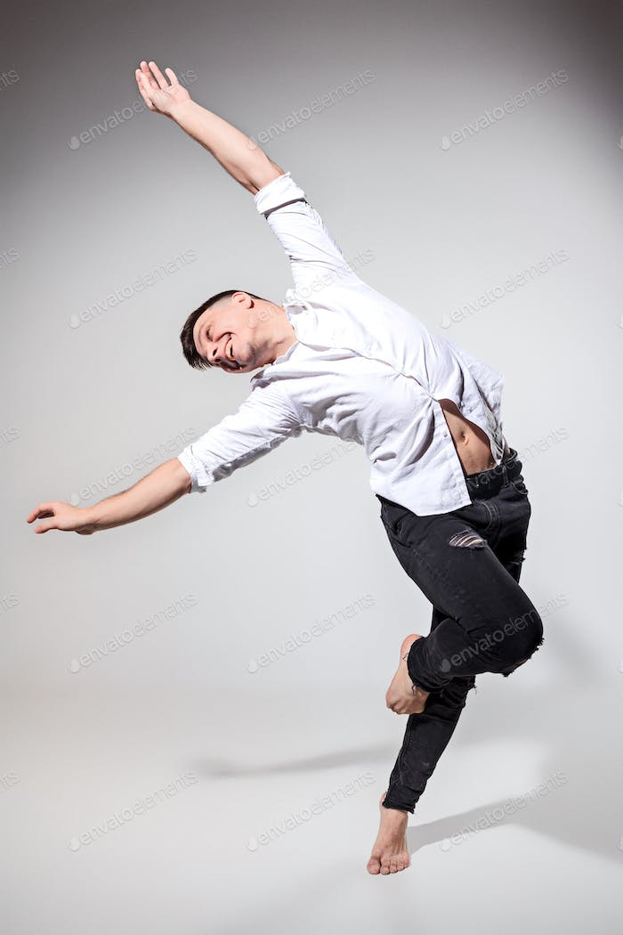 The young man dancing on gray