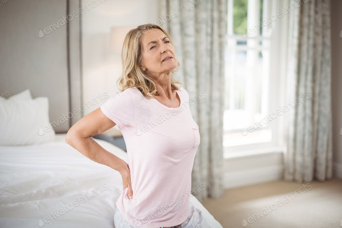 Senior woman having back pain in bedroom