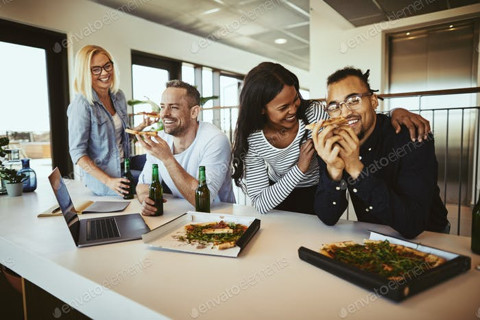 Diverse coworkers laughing and having pizza and beer after work