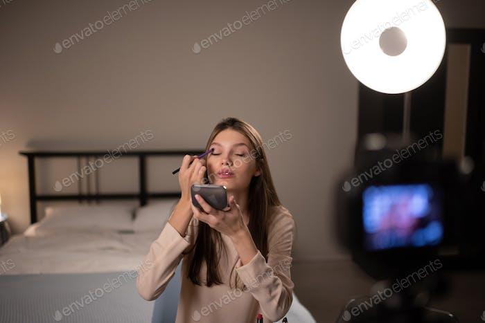 Weibliche Influencer Anwendung Lidschatten für Kamera