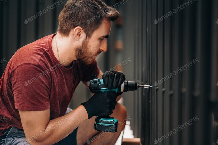 Handyman using a cordless screwdriver and drilling screws in metal fence