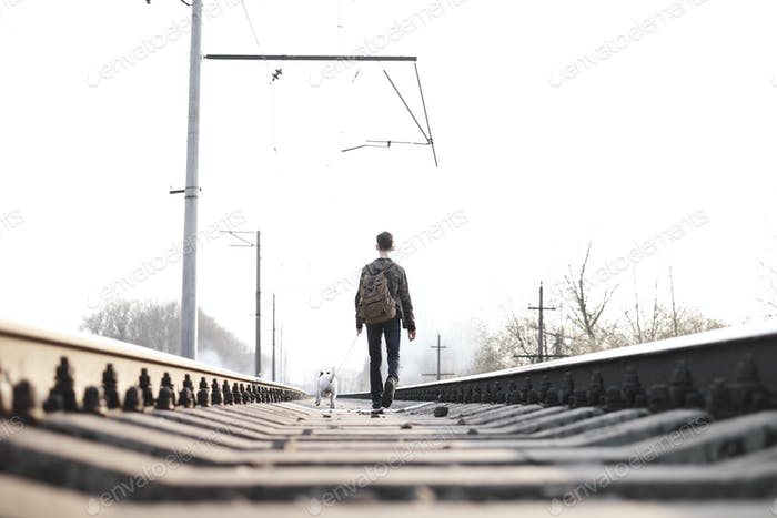 Teenager on railway walking with small white dog