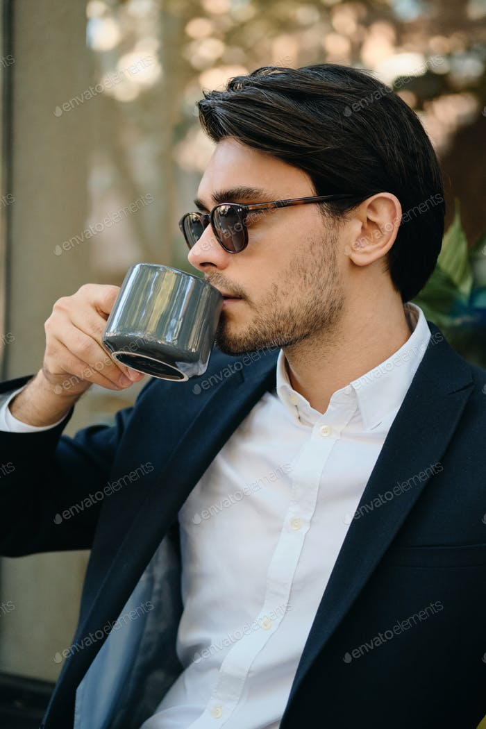 Attractive man in white shirt, classic jacket and sunglasses dreamily drinking coffee on city street
