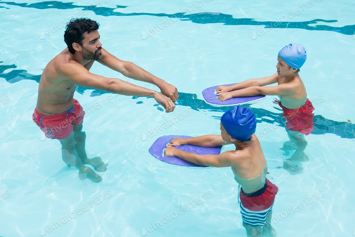 Coach assisting a kids in swimming in pool