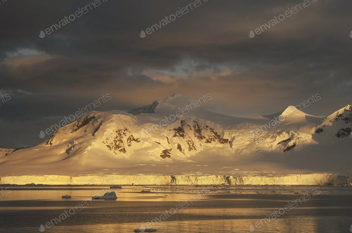 Sunset over the mountainous landscape of Antarctica.