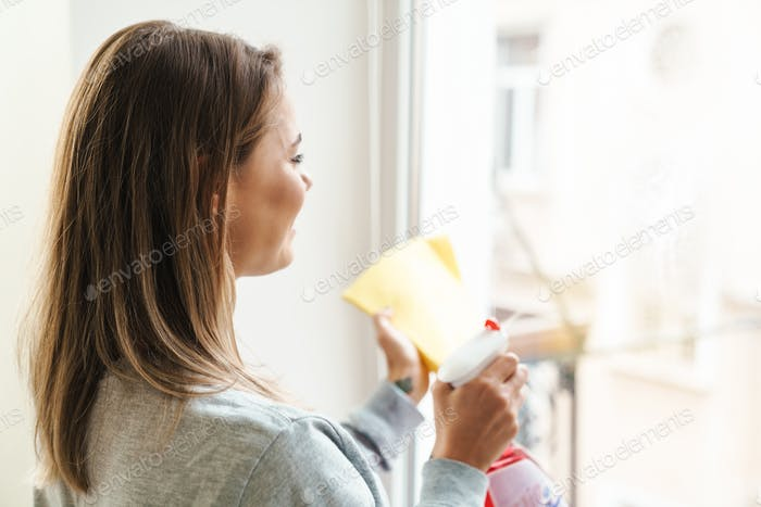 Photo of cheerful woman housewife smiling and cleaning window