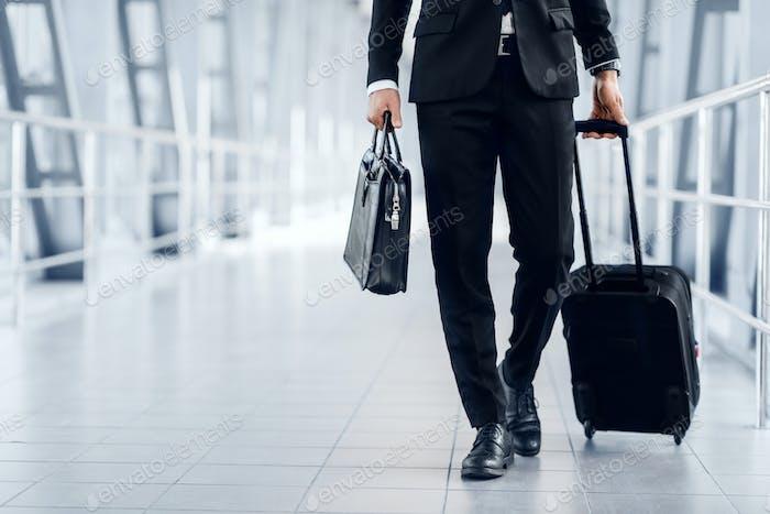 Неузнаваемый предприниматель в костюме, гуляющий по аэропорту