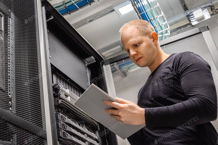 Male IT Professional Using Digital Tablet to Monitor Datacenter Status