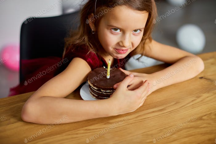A greedy little girl is wearing a birthday hat hold at a Birthday Cake, make faces