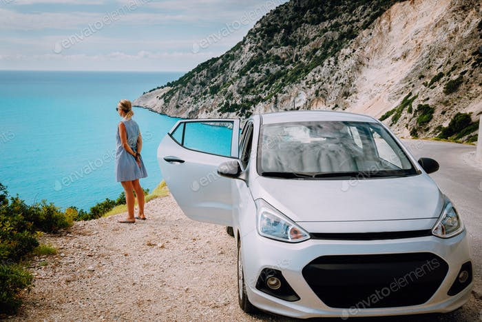 Women near rented car with open door enjoying Myrtos Beach. Travel vocation concept. Kefalonia