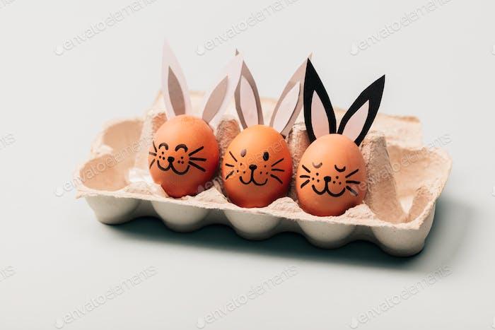 Drei Eierhasen stehen in einem Eierkarton.