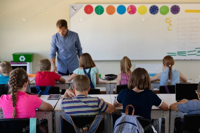 Male school teacher standing in an elementary school classroom with a group of school children