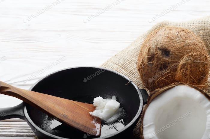 Kokosnuss, Schale mit Fleisch, Gusseisen Pfanne und Spachtel auf Hanf