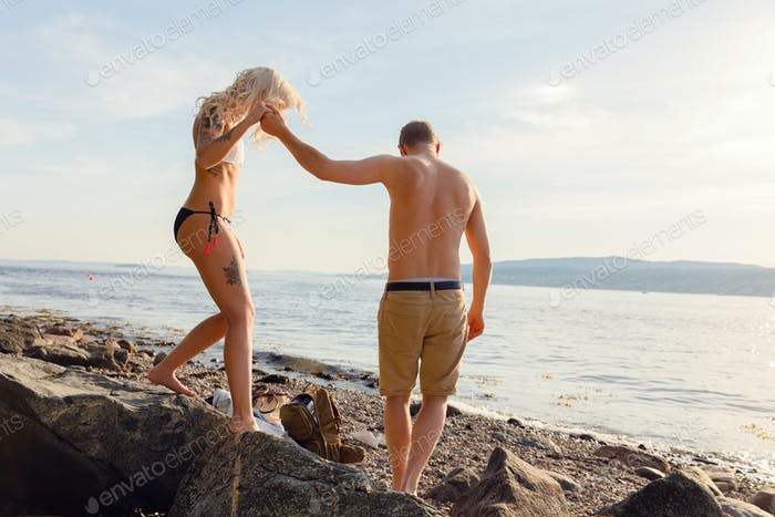 Romantic Man Holding Hand Helping Girlfriend On Rocks
