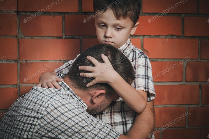 Portrait of sad son hugging his dad