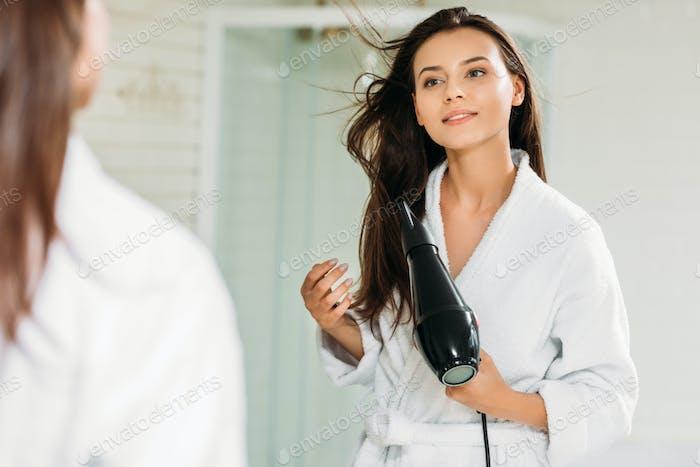 hermosa chica sonriente en albornoz usando secador de pelo en el baño