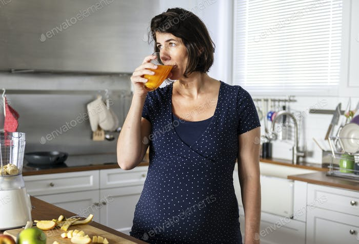 Pregnant woman drinking an orange juice